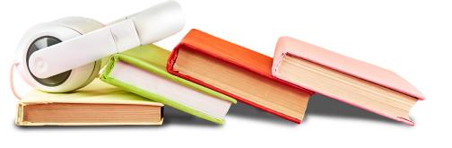 Böcker som ligger på en rad och ovanpå ligger ett par hörlurar