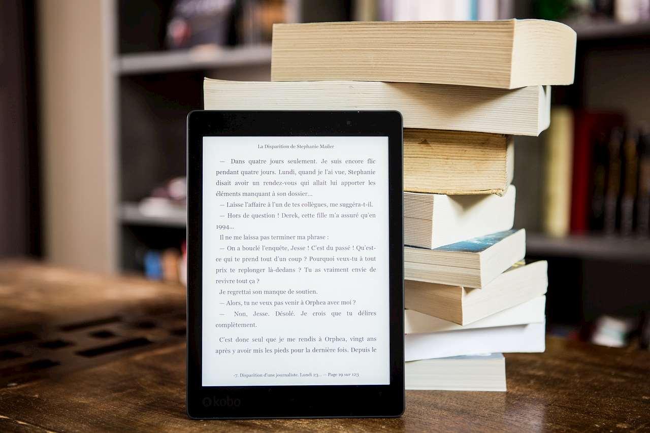 Bild på läsplatta framför en bokstapel