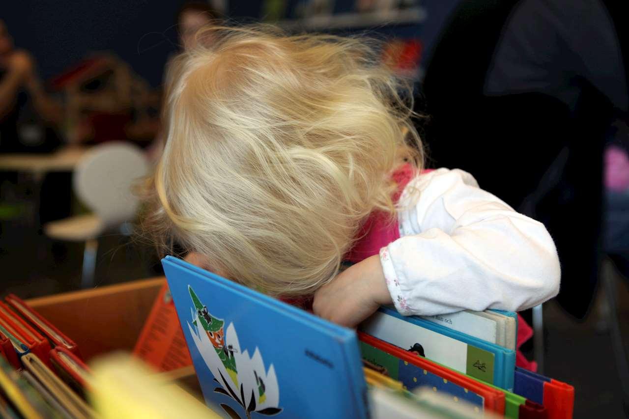 Ett barn tittar på böcker i ett boktråg